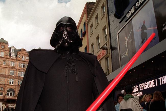 A Star Wars fan dressed as Darth Vader complete with lightsaber