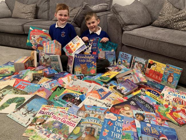 Max and Liam Hunter with the books they have collected