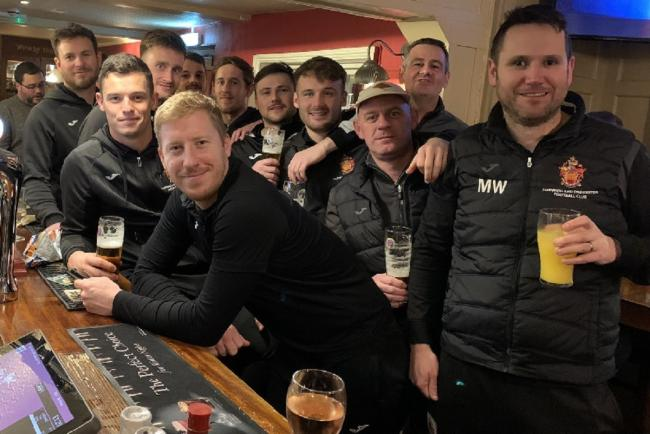 Cheers - Harwich and Parkeston's players and management, en route back to north Essex, stop off to celebrate their 1-0 victory at Hackney Wick