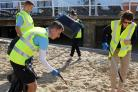 Clean up: Clacton Pier staff picking up litter on West Beach, Clacton