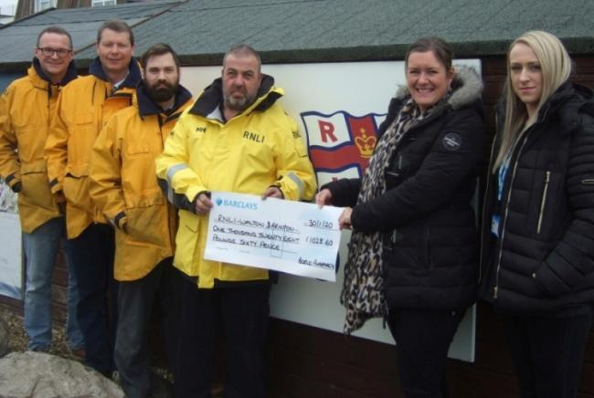 LARGE DONATION: Walton and Frinton RNLI volunteers Gary Pope, Peter Helland and Euan Wilkinson look on as Gemma Robb and Natalie King of Borno Chemist present the cheque to station mechanic Karl Bigwood Picture: RNLI/Miranda Rayner