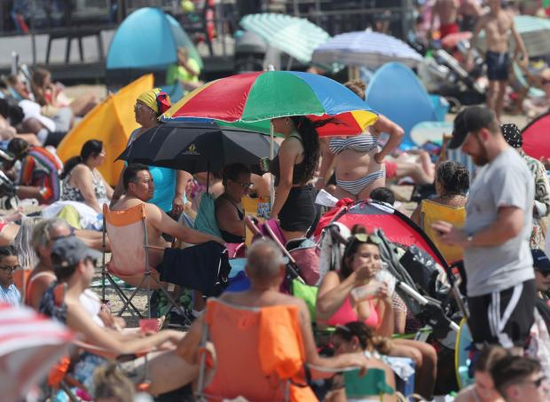 Clacton and Frinton Gazette: Take shelter! - Umbrellas to protect families against the hot sunshine