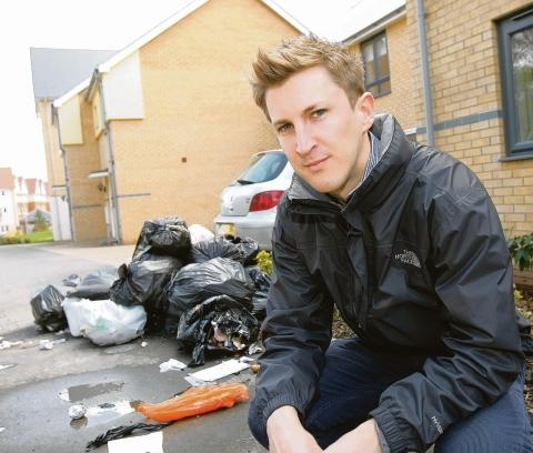 Dumped – Ian Oxborrow outside his home, with rubbish piled up on his driveway