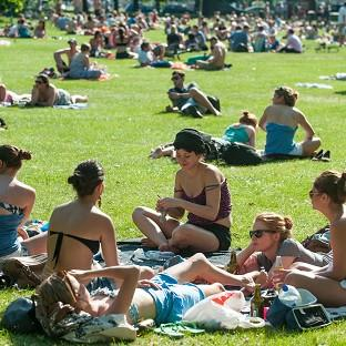 People soak up the sun on Clapham Common, south London, as the UK experiences a weekend of hot weather