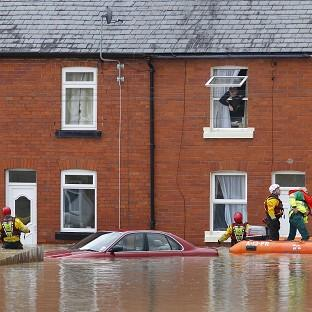 A man looks out of a window as a crew from the RNLI and paramedics pass a submerged car in St Asaph, Denbighs