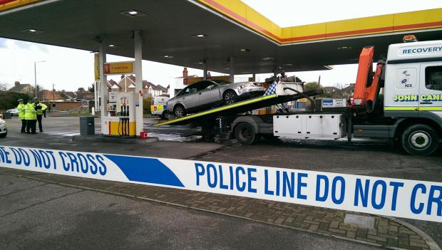 Police officers injured trying to stop a suspect - who crashed into a petrol station while dragging them along