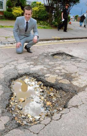 Councillor Pierre Oxley demonstrates monster pothole
