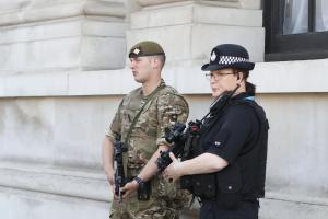 Members of the army join police officers on Whitehall, London, after Scotland Yard announced armed troops will be deployed to guard