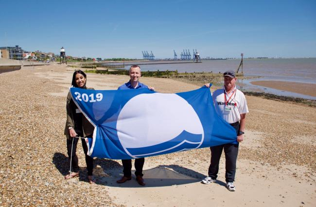 Seafronts business manager Yana Humphreys, Mike Carran head of sport and leisure, and Beach Patrol warden Andy Brouard with a Blue Flag at Dovercourt Bay Beach. Picture: Matt Cattermole/TDC